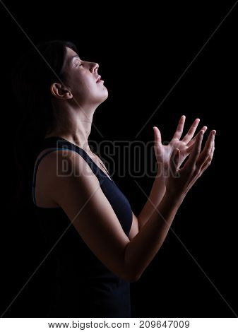 Low key of a faithful woman praying and feeling the presence or being touched by god. Arms outstretched in worship, head up and eyes closed in religious fervor. Black background.