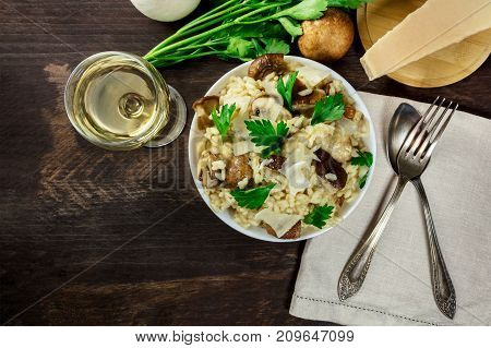 An overhead photo of a mushroom risotto, with champignons, fresh parsley, porcini, Parmesan cheese, a glass of white wine, a fork and a spoon, and a place for text, on a dark rustic texture