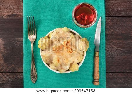 An overhead photo of a cauliflower gratin on a teal tablecloth with a glass of rose wine, a fork, a knife, and a place for text