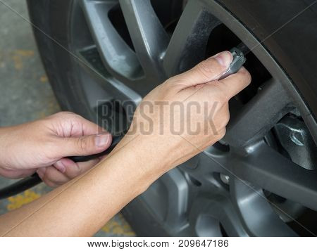 hand man fill the air for tires.