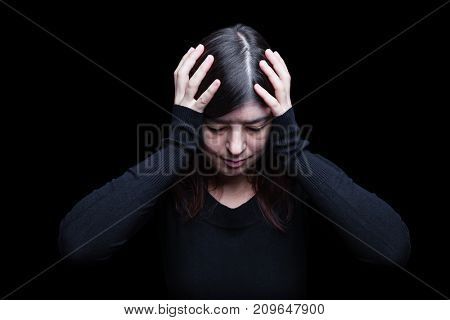 Distressed, woman holding the head with the hands, on a black or dark background. Concept for migraine, headache, pain, depression, despair, suffer, worried, frustration.
