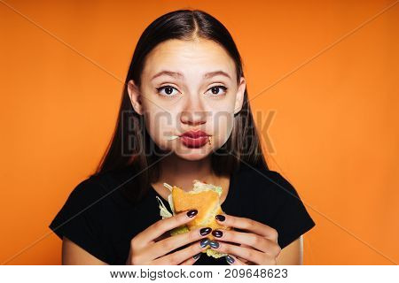 beautiful young girl wants to lose weight, but eagerly eats a harmful calorie burger