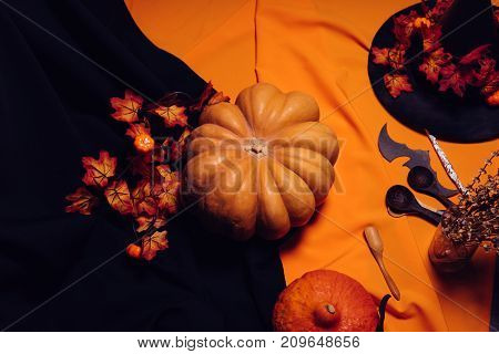 composition for decorating the house for halloween, lie yellow and orange pumpkins on each other, a big black witch hat decorated with yellow autumn leaves, wooden spoons