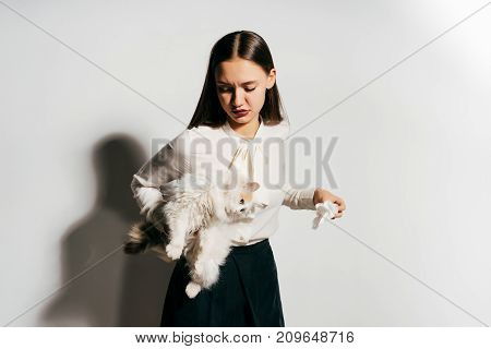a beautiful young girl celebrates looking displeased because she is holding a cat, but she is allergic to animals