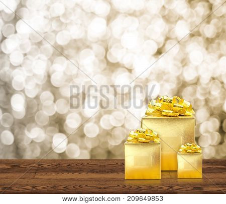 Golden Gift Box On Wood Table Top With Blur Sparkling Gold Bokeh Abstract Background,panoramic Banne