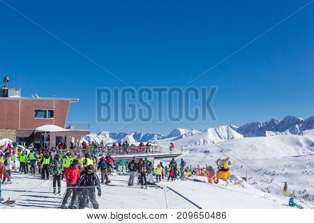 PYRENEES ANDORRA - FEBRUARY 9 2017: People in mountains in ski resort. Riding stand near cafe at the beginning of descent on the route. Sunny winter day