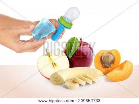 Woman holding baby nibbler and sliced fruits on white background