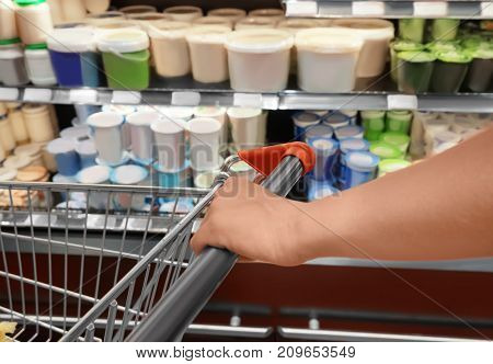 Young woman with trolley choosing milk products in supermarket