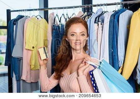 attractive woman with shopping bags and credit card in boutique