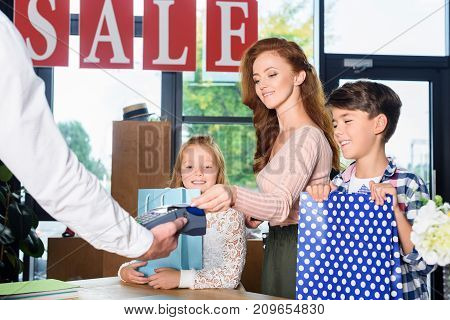 mother and children paying with credit card in boutique