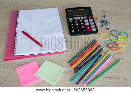 office supplies business accessories with color pencils and notebook on wooden table. Office tools