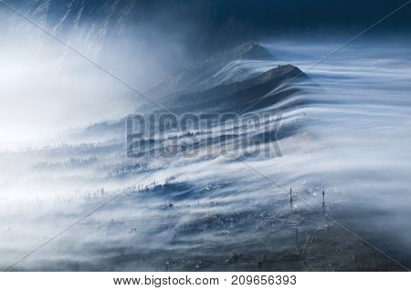 Mist Flowing over Cemoro Lawang and into Crater Gunung Bromo or Mount Bromo area Java Indonesia.