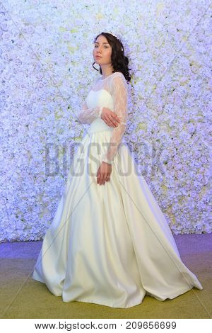 PERM RUSSIA - FEB 12 2017: Pretty model bride in white dress poses near flowers wall at Wedding Fair Perm 2017