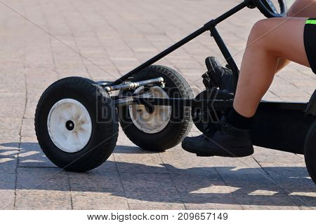 Legs of man riding on foot-operated four-wheeler at sunny day