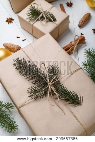 Christmas background with gift boxes wrapped in kraft paper fir tree branches golden glass balls pine cones cinnamon sticks and stars anise on white wooden background