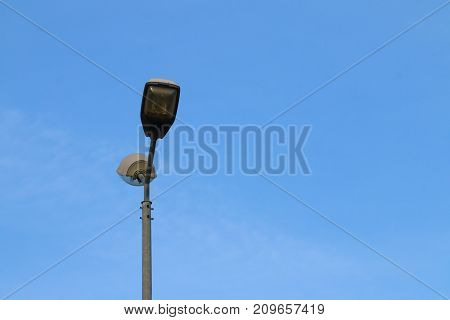 Modern lonely tall street light and bright blue sky with clouds