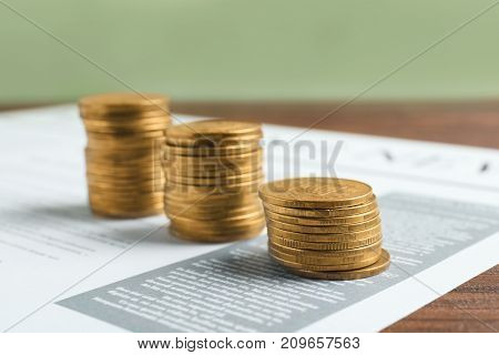 Stacks of coins on newspaper, closeup