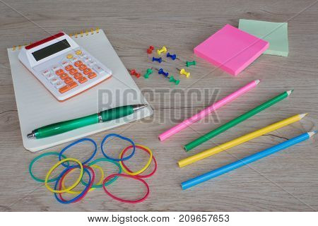 Colour pencils calculator notebook and office stationery at table. business accessories on wooden table