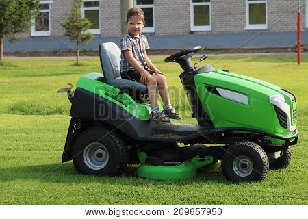 Little boy sits on lawn on green grass near building at summer day