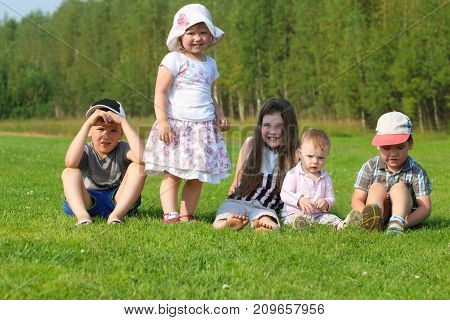 Five happy children sit and stand on green grass on summer field