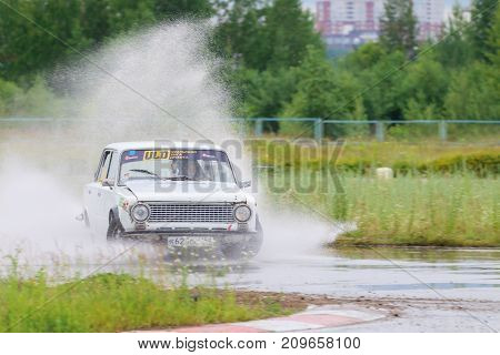 PERM RUSSIA - JUL 22 2017: Drifting white car with splash at Open Ural Championship Drift 2017