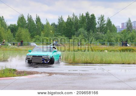 PERM RUSSIA - JUL 22 2017: Drifting green car move on wet asphalt track at Open Ural Championship Drift 2017