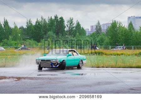 PERM RUSSIA - JUL 22 2017: Drifting green car on wet asphalt track at Open Ural Championship Drift 2017