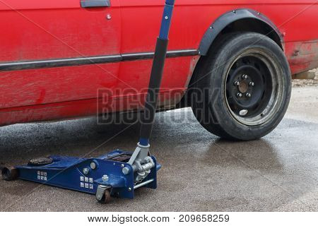 Part of car and tool for car repairing - levelling jack on asphalt outdoor