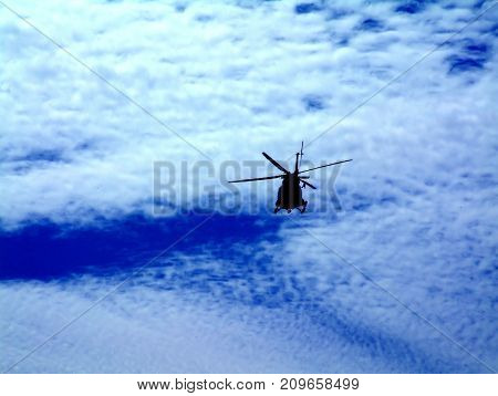 Helicopter Silhouette on Dark Blue Sky with Cloud Bank
