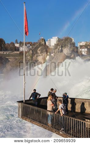 Laufen, Switzerland - 18 October, 2017: people on the observation platform at the Rhine Falls. The Rhine Falls is the largest waterfall in Europe, located on the border between the Swiss cantons of Zurich and Schaffhausen.