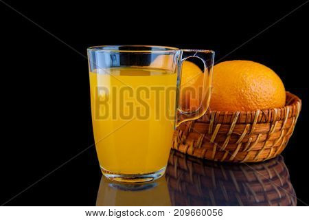 Orange juice - glass with oranges on black background