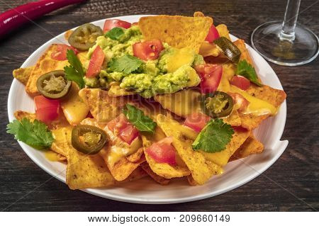A photo of nachos with queso, traditional Mexican snack, on a rustic background with a red hot chili pepper
