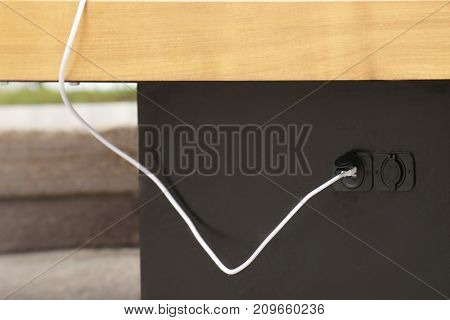 Wire of mobile phone charger on bench with solar panel