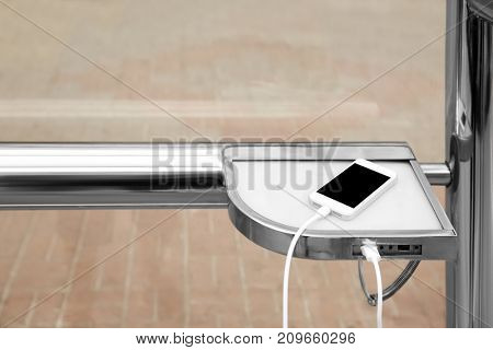 Charging mobile phone, outdoors