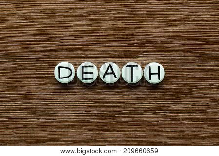 White round pills with inscription DEATH on brown wooden board background. Illustration for health harm or drug side effects.