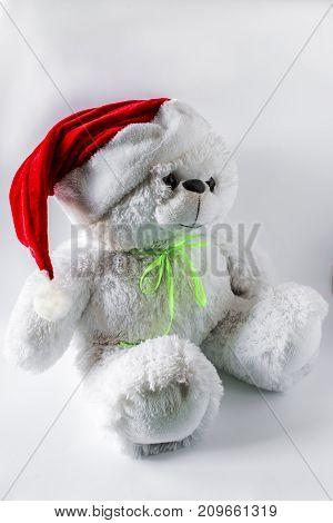 Toy Teddy Bear Wearing Santa Hat, On A Light Background.