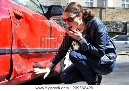 Shocked woman looks a damage of her car. Real people. Copy space