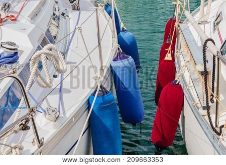 detail of two boats anchored with the typical colored fenders /two boats anchored at the  harbor