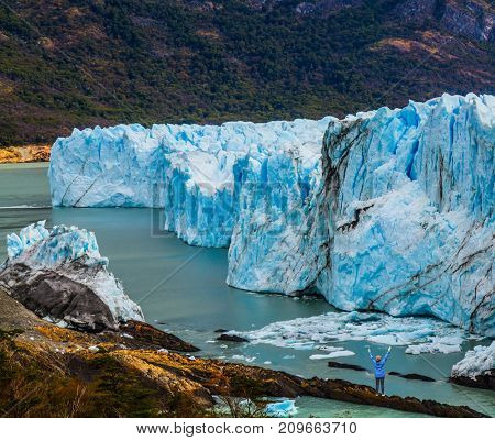 Patagonia. Unique lake and glacier Perito Moreno,  in a mountain valley. Woman -  tourist enthusiastically raised her hands. The concept of  exotic and extreme tourism