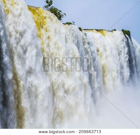Water splashes and fog over Iguazu Falls in South America, on the border of three countries. Concept of active and extreme tourism