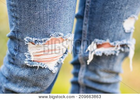 Ragged knee-deep blue jeans close-up with blurred background