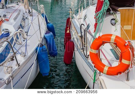 two boats anchored at the  harbor /detail of two boats anchored with the typical colored fenders and the characteristic orange life-buoy