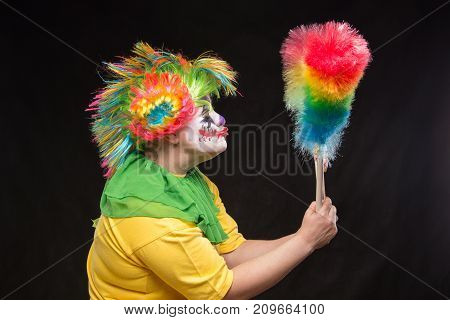 Scary clown with colorful mohawk and a smile with a lollipop on a black background