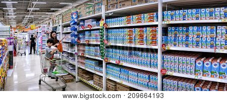 BANGKOK THAILAND - OCTOBER 13: Mother and child shops for packaged milk in the hypermarket aisle in BigC Extra Petchkasem in Bangkok on October 13 2017.