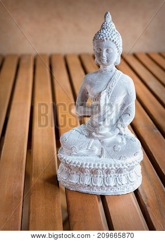 White Buddha statue on wooden background with copy space. Inspiration sculpture for meditation or mindfulness.