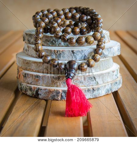 Close up of wood mala beads traditionally used in prayer and meditation. Essential accessory for mindfulness or practice yoga.