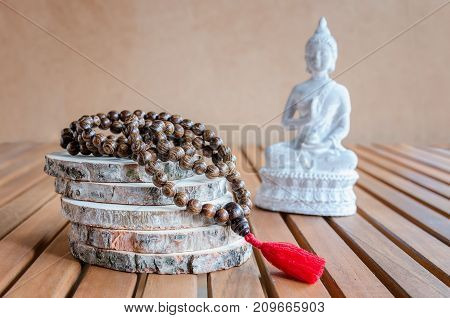 Close up of wood mala beads and white statue of Buddha. Essential accessories for metidation or practice yoga.