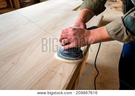 Man sanding a wood with orbital sander in woodwork workshop