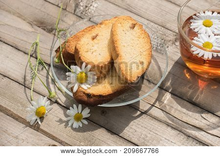 Herbal tea with white daisies and rusks on a glass plate on a wooden table in summer