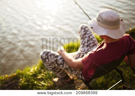 Young man fishing at pond and enjoying hobby activities